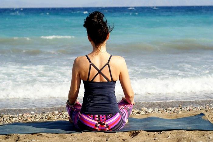 donna medita sulla spiaggia in centratura